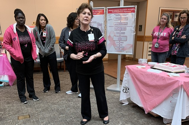 Madigan Army Medical Center's Breast Cancer Pathway Clinical Coordinator, Genevieve Fuller, an advanced registered nurse practitioner, welcomes people to a 25th anniversary celebration of the program and clinic at Madigan on Joint Base Lewis-McChord, Wash., on Oct. 16.