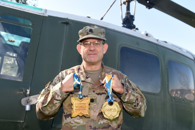 Lt. Col. Pete Caragher, Deputy G-3, 85th U.S. Army Support Command, holds two medals that he won in a Brazilian Jiu-Jitsu competition one is a 2014 World Masters gold medal and the other is a first place gold medal from the 2013 International Brazilian Jiu-Jitsu Federation Championship. Originally from Schiller Park, Illinois, Caragher became interested in Jiu-Jitsu during his second tour as an Active Guard/Reserve officer based in California. He practices Jiu-Jitsu three or four times a week and currently holds a brown belt in the sport. His sports background includes participation in wrestling, hockey, football, cross training and the triathlon. Caragher joined the Army in 1985 and graduated from the Reserve Officer Training Corp at Northern Illinois University. He was awarded the Meritorious Service Medal for his service on a combat tour in Iraq from May 2006 until August 2007. (U.S. Army Reserve photo by Sgt. David Lietz)