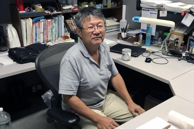 Hiromitsu Arakaki sits at his desk at Okinawa Area Office, Japan Engineer District.