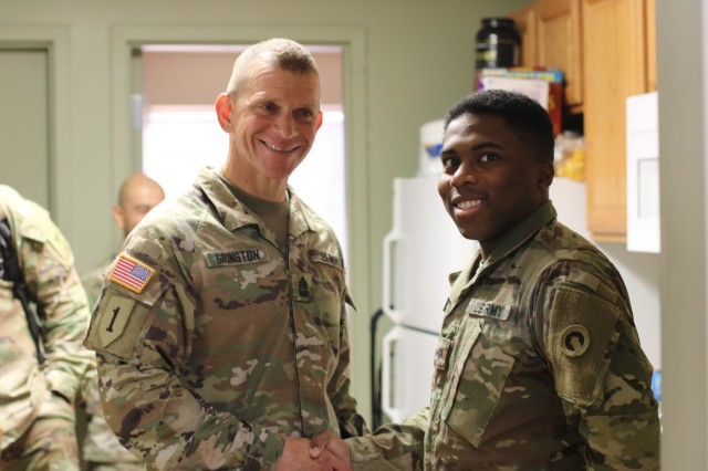 Sgt. Major of the Army Micheal A. Grinston, awards Spc. Khari Johnson, 1st Theater Sustainment Command, a coin of excellence for maintaining high standards, during his visit to Fort Knox, Ky. (U.S. Army photo by Sgt. Nahjier Williams)