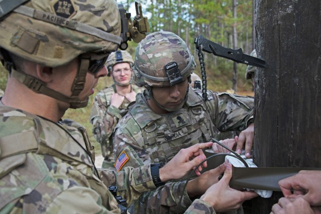 Soldiers assigned to 92nd Engineer Battalion, 3rd Infantry Division, attach composition C-4 explosives to a log for the timber cutting portion of a demolition range training event, Oct. 17, 2019, at Fort Stewart, Georgia. This demolition range was the first major training event for the Engineers Bn. after their return from supporting the war effort in the Middle East. (U.S. Army photo by Sgt. Arjenis Nunez)