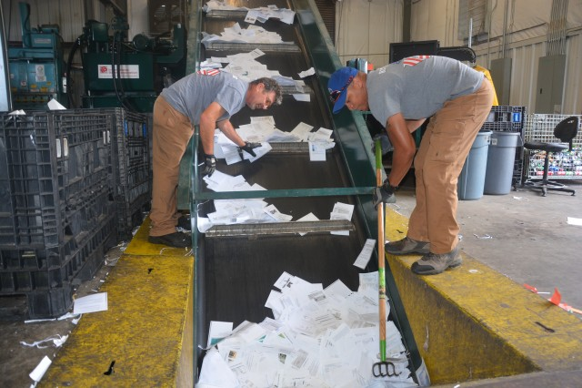 Stephen Nay (left) and David Jackson (right), motor vehicle operators with Fort Gordon Recycling, hand sort paper to ensure quality with the help of a baler. The machine takes the paper and forces it into a large bale that holds all the material together.
