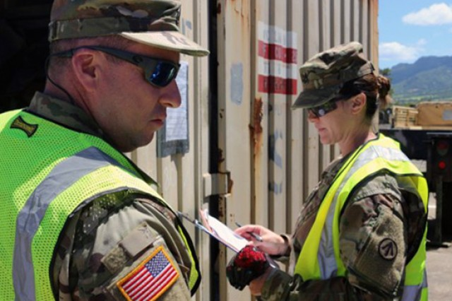 Sgts. 1st Class Amanda Reilly and Dennis Bordelon, 1192nd DDST from New Orleans, Louisiana, inspect the contents of containers at the 25th CAB motor pool on July 24. (Photo Credit: Donna Klapakis (SDDC)