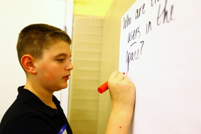 """Peter Leahy, 12, writes down ideas his small group created as they answer, """"Who are the users in the space?"""" He is a seventh grader at Central Middle School."""