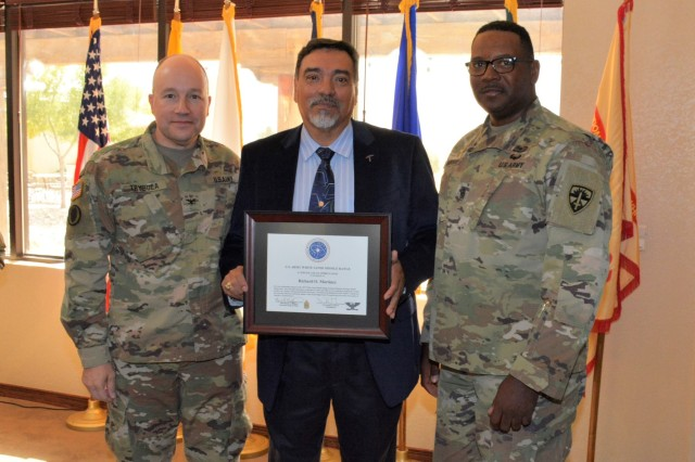 White Sands Missile Range Commander Col. David C. Trybula, left, and Command Sgt. Maj. William A. Wofford, right, present Richard O. Martinez an award for speaking at the National Hispanic Heritage Month observance on Oct. 24, 2019 at White Sands Missile Range.