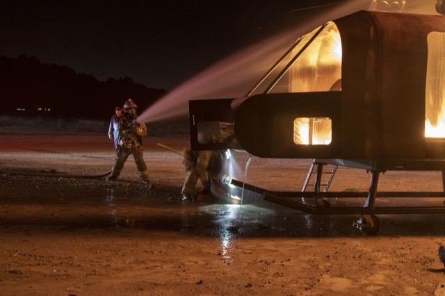 Pfc. Kyler Coppens, a firefighter assigned to 463rd Engineer Firefighter Detachment, U.S. Army Reserve suppresses flames from a training rotary-wing aircraft fire allowing another firefighter to rescue a simulated casualty during a culminating training exercise at White Sands Missile Range, N.M., Oct. 21, 2019.  463rd trained and validated with 5th Armored Brigade, First Army Division West in preparation for an upcoming deployment to the middle-east. (U.S. Army photo by Staff Sgt. Timothy Gray, 5th Armored Brigade)