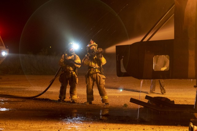 Pfc. Kyler Coppens and another firefighter assigned to 463rd Engineer Firefighter Detachment, U.S. Army Reserve suppresses flames from a training rotary-wing aircraft fire during a culminating training exercise at White Sands Missile Range, N.M., Oct. 21, 2019.  463rd trained and validated with 5th Armored Brigade, First Army Division West in preparation for an upcoming deployment to the middle-east. (U.S. Army photo by Staff Sgt. Timothy Gray, 5th Armored Brigade)
