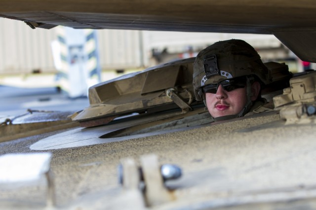 An Army Soldier with 1st Armored Brigade Combat Team, 1st Infantry Division, prepares to move a staged M1 Abrams Tank at the port of Bremerhaven, Germany Oct. 18, 2019. The Big Red One Soldiers have been deployed throughout Eastern Europe for the last nine months as a rotational force in support of U.S. Army Europe and Atlantic Resolve. (U.S. Army photo by Sgt. Thomas Mort)