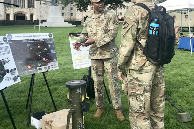 Maj. Frankie Jackson speaks to a cadet at the United States Military Academy at West Point about the career opportunities and advantages of serving in the Army Acquisition Corps. The cadet is wearing Oculus Virtual Reality googles, which give cadets a first-person view of obstacle planning in a tactical environment, emplacement of the Terrain Shaping capabilities on the battlefield, and viewing the effects it has on targets. Jackson is Assistant Product Manager for Terrain Shaping Obstacles, Project Manager Close Combat Systems, an organization within the Joint Program Executive Office Armaments and Ammunition at Picatinny Arsenal, N.J.