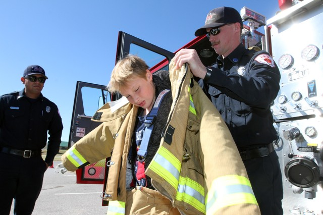 Tucker Tackaberry, 10, puts on a bunker suit with help from Fort Sill firefighter Zac Howell Oct. 26, 2019, during the Fall Festival at LETRA. The firefighters were there to provide any needed assistance, including water rescues, as well as to showcase a fire engine, and a brush truck. October is fire prevention month so the firefighters, including Rafael Hernandez (left) answered peoples' burning questions, too.