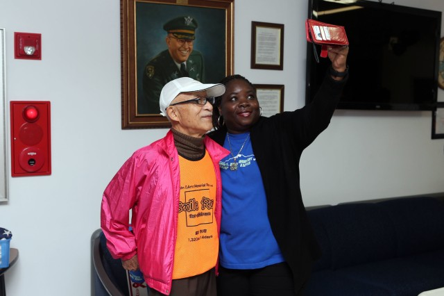 """Gwendolyn Baxter-Oakley, principal of John O. Arnn Elementary School, takes a selfie with Aki Sago, director of the """"Smile Run,"""" in front of a portrait of Arnn at the school Oct. 27 before the start of the race."""