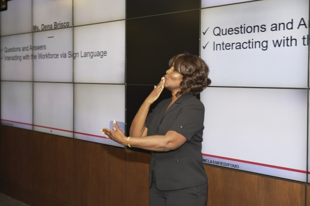 """Dena Brisco, who is hearing impaired, greets the audience with a """"good morning"""" during her National Disability Employment Awareness Month presentation to Army Materiel Command employees at AMC Headquarters, Oct. 23. Brisco works as a staff assistant in the G-6, Business Management Division at AMC Headquarters."""