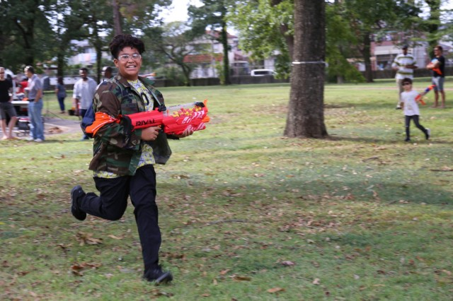 """A participant in the Camp Zama Youth Sports and Fitness-hosted """"Humans vs. Zombies"""" event runs in pursuit of undead enemies Oct. 26 at Sagamihara Family Housing Area, Japan. (U.S. Army photo by Noriko Kudo)"""