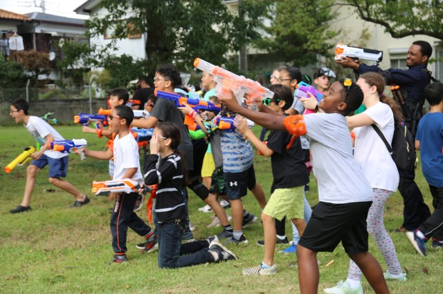 """Youth participants from the Camp Zama community shoot at zombies with foam-dart guns during the Camp Zama Youth Sports and Fitness-hosted """"Humans vs. Zombies"""" event Oct. 26 at Sagamihara Family Housing Area, Japan. (U.S. Army photo by Noriko Kudo)"""