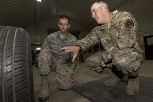 Air Force Tech. Sgt. Jason Ludlum, right, 368th Training Squadron ground transport instructor, talks tire changing with Airman 1st Class Joshua Sandoval. Sandoval recently assisted an injured flight attendant while on his way to Fort Leonard Wood, Missouri.