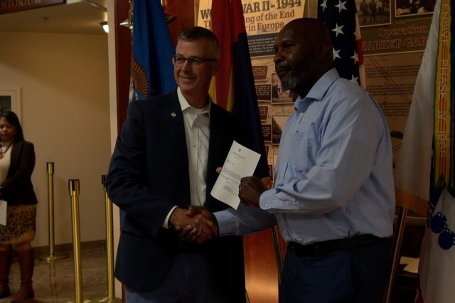 Jeffrey Jennings, Deputy to the Commanding General, U. S. Army Intelligence Center of Excellence (USAICoE) presents a letter to Samuel Brown a mentor who participated in the 2019 USAICoE Mentorship Program at a ceremony on Fort Huachuca, Ariz. (U.S. Army photo by Thom Williams)