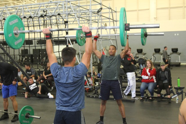 Capt. Tarell Roberts, a Captains Career Course student, and Staff Sgt. Richard Hernandez, Headquarters and Headquarters Support, 434th Field Artillery Brigade, keep pushing during the synchro thrusters portion of WOD 3 at the Ghost Thrusters team competition Oct. 26, 2019.