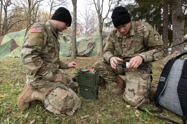 Army Spc. Josh Southerland (left) and Spc. Dillon Devore, both signal systems support specialists from Seymour, Ind., assigned to the 1st Squadron, 152nd Cavalry Regiment, 76th Infantry Brigade Combat Team, 38th Infantry Division, Indiana Army National Guard, set up an AN/PRC-150 multiband radio in a field at Le�� military training center in Slovakia, Oct. 29, 2019.