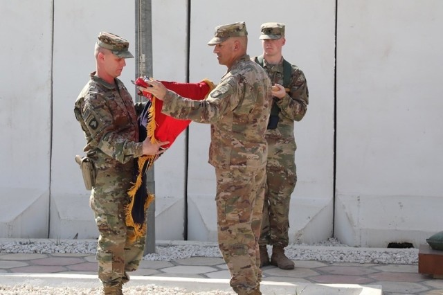 Col. Derek Thomson, left, commander of 1st Brigade Combat Team, 101st Airborne Division, and Command Sgt. Maj. Wray Gabelmann, the brigade's senior enlisted advisor, case the brigade colors officially ending their mission within Iraq. With about 2,000 Soldiers deployed across northern Iraq and in parts of Syria, the brigade represented most of Task Force Iraq that oversaw coalition support to Iraqi forces.
