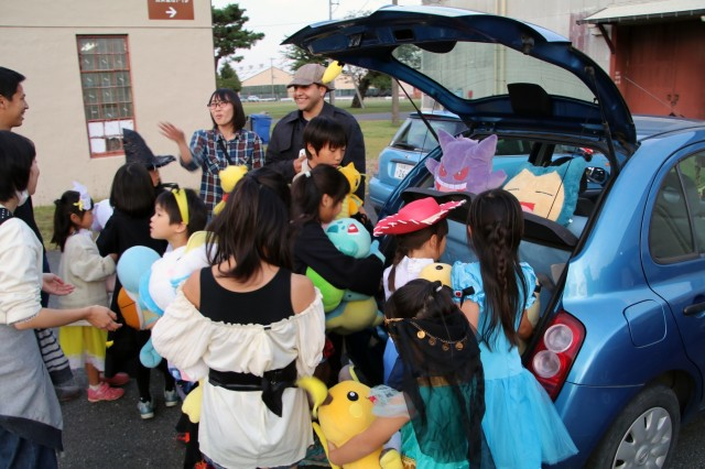 SAGAMIHARA, Japan - Pvt. Wilfredo Estremera, human resources specialist, Headquarters and Headquarters Battery, 38th Air Defense Artillery Brigade, gives away his stuffed animals to the youth of Chushin Children's Home during the 1st Annual 38th ADA Bde. Trunk-or-Treat event to deepen community ties at Sagami General Depot, Oct. 30. Estremera recognized some of the children from a recent volunteer English-proficiency program he attended and wanted to bring joy to the children.