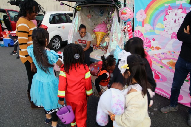 """SAGAMIHARA, Japan - Maj. Sirena Sias, signal officer, 38th Air Defense Artillery Brigade, gives candy to children during the 1st Annual 38th ADA Brigade Trunk-or-Treat event to deepen community ties at Sagami General Depot, Oct. 30. Sias' """"Candy Land"""" themed trunk was a favorite amongst many as her work received recognition as """"Best Trunk"""" by Capt. Frederick Sherman, Headquarters and Headquarters Battery, 38th ADA Bde. during the event's closing ceremony."""