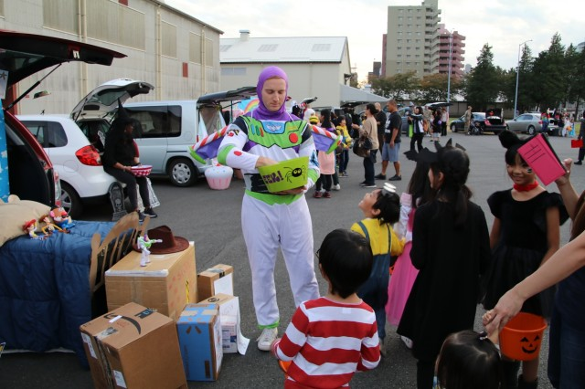"""SAGAMIHARA, Japan - Capt. Frederick Sherman, commander, Headquarters and Headquarters Battery, 38th Air Defense Artillery Brigade, hands out candy next to his """"Toy Story"""" inspired trunk to children of the local community to deepen ties with neighbors during the 1st Annual Trunk-or-Treat event at Sagami General Depot, Oct. 30. (U.S. Army photo by Sgt. Raquel Villalona, 38th Air Defense Artillery Public Affairs)"""