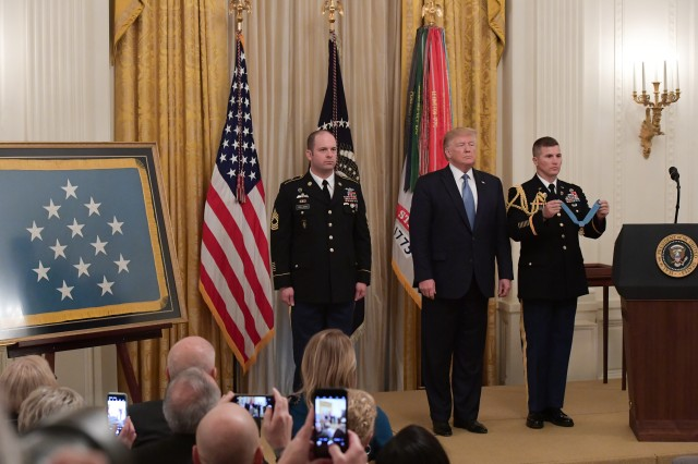 U.S. Army Master Sgt. Matthew O. Williams stands as the citation is read before receiving the Medal of Honor from President Donald J. Trump during a ceremony at the White House in Washington, D.C., Oct. 30, 2019. Williams was awarded the Medal of Honor for his actions while serving as a weapons sergeant with the Special Forces Operational Detachment Alpha 3336, Special Operations Task Force-33, in support of Operation Enduring Freedom in Afghanistan on April 6, 2008.