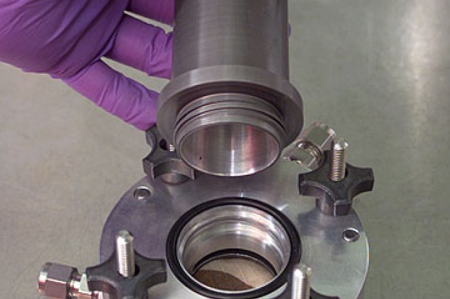 A swatch of cloth is loaded into the cup of the AVLAG, requiring two O-rings to keep it sealed and chemical agent from leaking. Assembling the many parts while wearing gloves can be challenging. The innovative SPITFIRE system created by Dugway Proving Ground uses the tension of clamps to keep the parts together, and offers greater ease and accuracy. Photo by Al Vogel, Dugway Public Affairs.