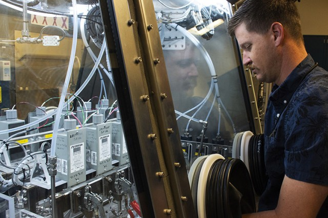 Aaron Rogers, project scientist at Dugway Proving Ground's West Desert Test Center, visually checks the controls that regulate how much chemical wafare agent challenges each swatch in the Swatch Permeation Test Fixture, Reengineered. In the next room the SPITFIRE system is monitored by computer, but occasional visual checks of the glovebox and its contents are done. Photo by Al Vogel, Dugway Public Affairs.