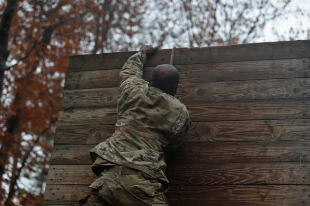"""Soldiers of 41st Engineer Battalion, 2nd Brigade Combat Team, 10th Mountain Division, continuously yell """"unleash the beast,"""" their company motto, while approaching a series of obstacles during physical training at a confidence course, October 31, 2019, at Fort Drum, New York. Mountain Sappers completed a dynamic warm-up before daylight, then climbed, weaved and crawled their way up, over and under each rain dampened obstacle while the sun rose. (U.S. Army photo by Staff Sgt. Paige Behringer)"""