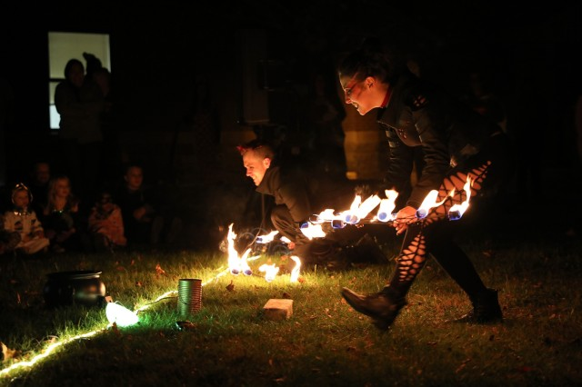 "Seth Hill and Jozette Gordon, both professional entertainers, perform a vampire themed fire dance for Soldiers and Families of 2nd Battalion, 15th Field Artillery Regiment, 2nd Brigade Combat Team, 10th Mountain Division, during the Allons ""Trunk or Treat"" Halloween event, October 30, 2019, at Fort Drum, New York. Children trick-or-treated through the battalion's basketball court and visited a small haunted house run by Allons Soldiers before settling in at nightfall for the fiery performance. (U.S. Army photo by Staff Sgt. Paige Behringer)"
