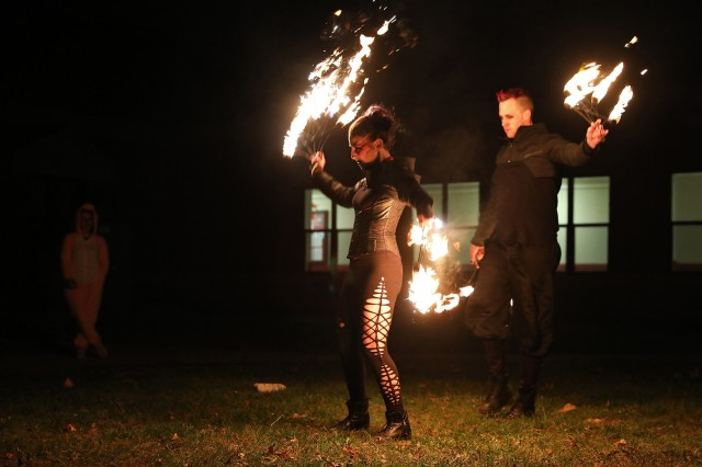 """Seth Hill and Jozette Gordon, both professional entertainers, perform a vampire themed fire dance for Soldiers and Families of 2nd Battalion, 15th Field Artillery Regiment, 2nd Brigade Combat Team, 10th Mountain Division, during the Allons """"Trunk or Treat"""" Halloween event, October 30, 2019, at Fort Drum, New York. Children trick-or-treated through the battalion's basketball court and visited a small haunted house run by Allons Soldiers before settling in at nightfall for the fiery performance. (U.S. Army photo by Staff Sgt. Paige Behringer)"""