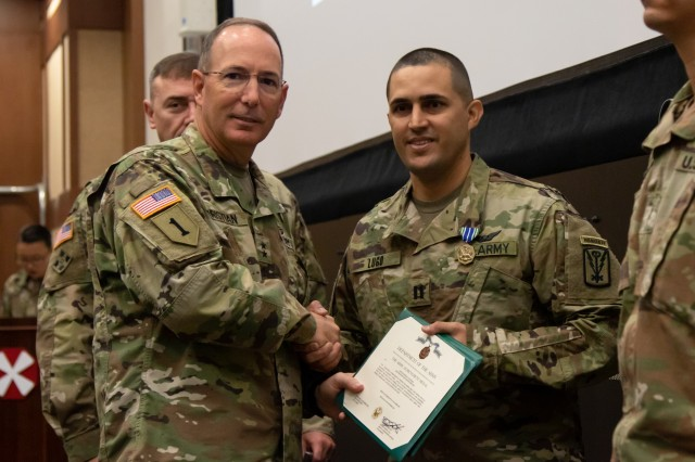 Maj. Gen. Daniel Christian, Eighth Army deputy commanding general, sustainment (left), and Capt. Lugo-Viera, A Company commander, 532nd Military Intelligence Battalion, 501st Military Intelligence Brigade, pose for a photo with Lugo-Viera's Army Achievement Medal for being selected as one of two officers to represent Eighth Army for the General Douglas MacArthur Leadership Award at the U.S. Army Pacific level. A ceremony was held for the Eighth Army finalists at Camp Humphreys, South Korea, Nov. 1. (U.S. Army photo by Pfc. Kang, Min-jin)