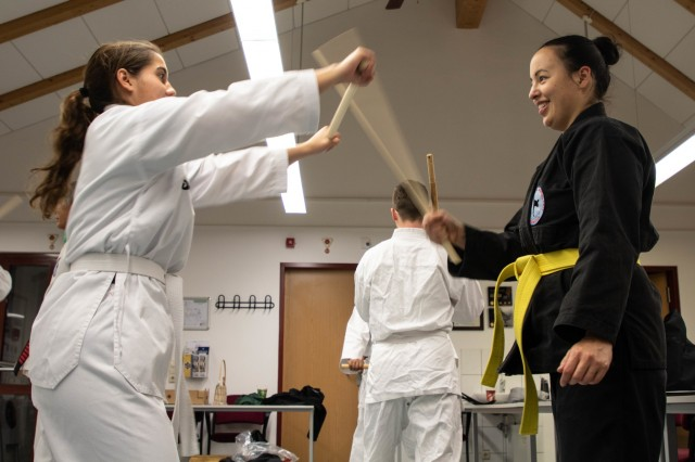 Sgt. Cassandra Viera, 164th Air Defense Artillery Brigade and Caroline Riggens, a member of the class, practice how to defend themselves while using a baton, during the martial arts self-defense class held on Katterbach Kaserne, Ansbach, Germany, Oct. 30, 2019. The martial arts class is designed for all skill levels and is open to anyone who has access to the installation to include family members, Department of Defense Civilians, and Local Nationals. (U.S. Army Photo by Pfc. Ashunteia' Smith)