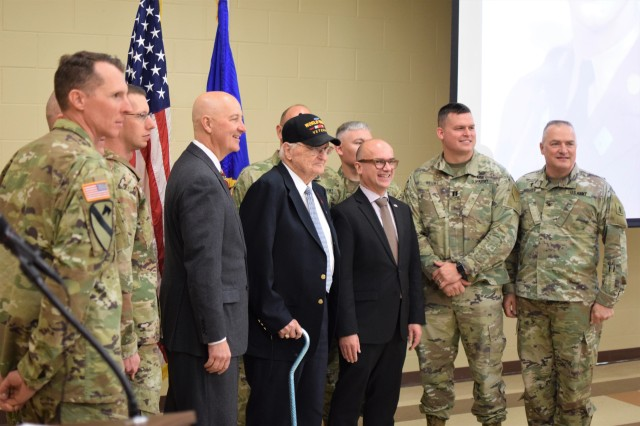 WWII veteran Edward Morrissette is joined by Nebraska Governor Pete Ricketts, French Consul General Guillaume Lacroix, and soldiers in attendance at an award ceremony Oct. 30, 2019, at the Omaha Army Reserve Center in Elkhorn, Neb. Morrissette served with the 16th Infantry Regiment, 1st Infantry Division, in seven campaigns and multiple beach landings, including Omaha Beach on D-Day June 6, 1944, and was nominated for the award by his family.