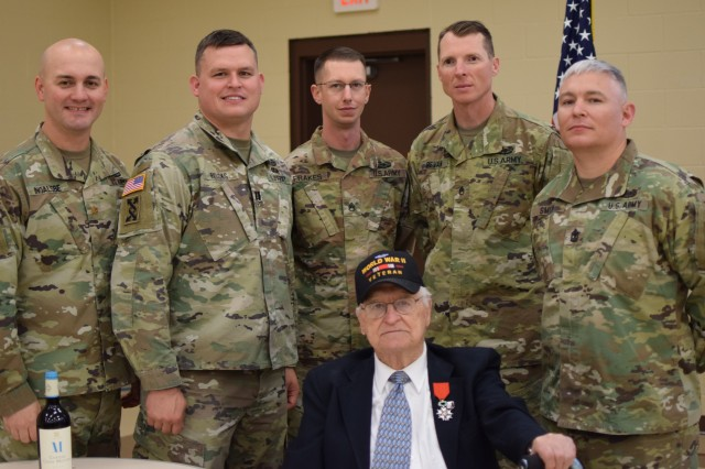 Nebraska Army National Guard Soldiers from the 1st Infantry Division's Main Command Post - Operational Detachment gather for a photo with Big Red One WWII veteran Edward Morrissette after he received the French Legion of Honor in a special ceremony Oct. 30, 2019, at the Omaha Army Reserve Center in Elkhorn, Neb. Morrissette served with the 16th Infantry Regiment, 1st Infantry Division, in seven campaigns and multiple beach landings, including Omaha Beach on D-Day June 6, 1944, and was nominated for the award by his family.