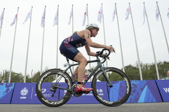 U.S. Air Force Maj. Judith Coyle of the U.S. Armed Forces triathlon team races a bicycle on her way to win gold in the 2019 CISM Military World Games in Wuhan, China Oct. 26, 2019. (DoD photo by EJ Hersom)