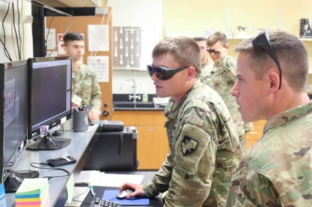 Class of 2021 Cadet Jacob Bohnemann and Capt. Joseph Fasone aim the 1 kilowatt laser in the high energy laser lab in Bartlett Hall.
