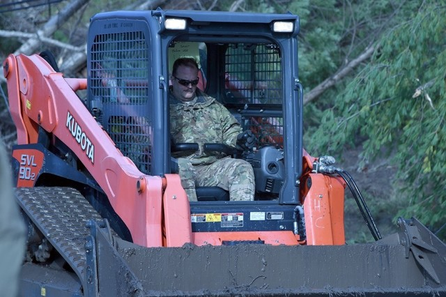 Master Sgt. Dave Taylor assigned to the 174th Attack Wing, Syracuse, New York is driving a Kubota Skid Steer that will help push debris away from roadways. This is in response to the New York National Guard activation Gov. Andrew Cuomo initiated on November 1 for damage caused by rain and winds.