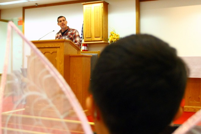 "Chaplain (1st Lt.) Philip Morlock, 2-4th FA, gives a sermonette Oct. 31, 2019, during Hallelujah Harvest as ""Tinkerbell"" listens at Frontier Chapel Center."