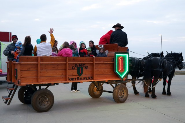 Soldiers and their Families participate in a wagon ride at the Headquarters and Headquarters Battalion Halloween party at HHBn's motor pool at Fort Riley, Kansas, on October 29, 2019. The wagon ride was offered by the Commanding General's Mounted Color Guard for the duration of the event. (U.S. Army Photo by Pfc. Jared Simmons)