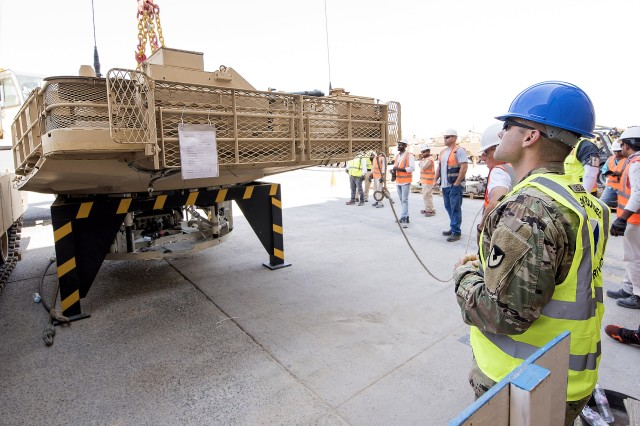 Sgt. 1st Class. Robert Ford, quality assurance for tanks, 401st Army Field Support Battalion-Kuwait, watches as contractors at Army Prepositioned Stocks-5 work to lift a 30-ton turret, Camp Arifjan, Kuwait, Sept. 23. Ford said his role in this kind of maintenance operation is to ensure safety and verify the quality of work on behalf of the government.