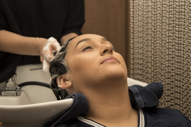"""Spc. Cassandra Cross, 3rd Cavalry Regiment, receives a shampoo at Tangerine Salon, Frisco, Texas, Nov. 2. The Cowboys' charity provided complimentary makeovers at the salon as part of their """"Salute to Service"""" weekend. (U.S. Army photo by Pfc. Alisha Edwards; 7th Mobile Public Affairs Detachment)"""
