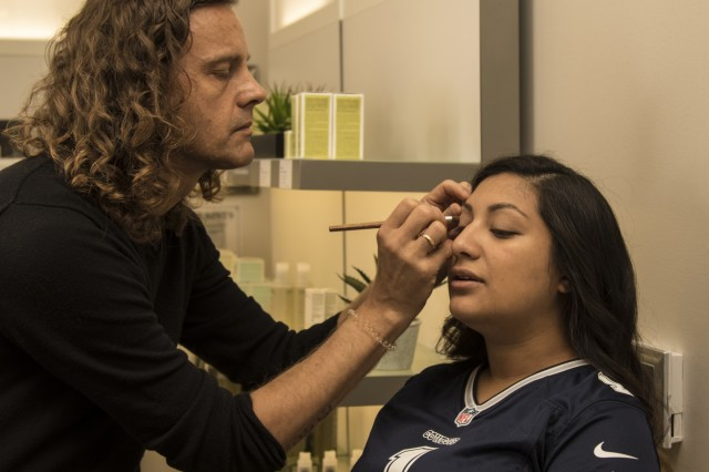 """Kevin Blackwell, beautician, applies makeup to Gabi Lopez, wife of Staff Sgt. Vidal Lopez, 3rd Security Force assistance Brigade, at Tangerine Salon, Frisco, Texas, Nov. 2. The Cowboys charity provided complimentary makeovers as part of their """"Salute to Service"""" weekend. (U.S. Army photo by Pfc. Alisha Edwards; 7th Mobile Public Affairs Detachment)"""