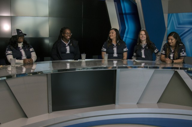 (left to right) Spc. Alicia Key-Jones, Spc. Jasmine Scott, Spc. Cassandra Cross, Spc. Leigha Power, and Gabi Lopez, sit at the media table in the Cowboys' media room at The Star in Frisco, Texas, Nov. 2nd. The five women were given a tour of the Cowboys' Headquarters facility as part of their visit. (U.S. Army photo by Pfc. Alisha Edwards; 7th Mobile Public Affairs Detachment)
