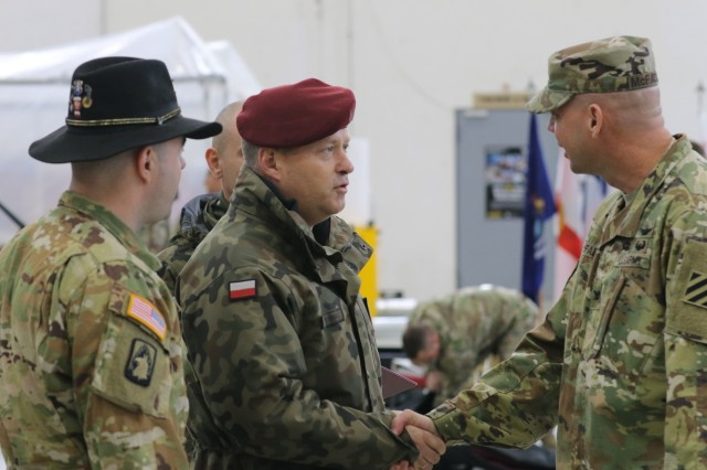 Col. Michael S. McFadden, Commander of the 3rd Combat Aviation Brigade (3rd CAB), greets a Polish Armed Forces Officer at the 1st Combat Aviation Brigade (1st CAB) to 3rd Combat Aviation Brigade (3rd CAB) Transfer of Authority (TOA) ceremony, Nov. 1, 2019, Illesheim, Germany. 3rd CAB will be working with NATO allies and partners such as Poland, during their nine-month rotation in support of Atlantic Resolve. (U.S. Army photo by Spc. Joseph Knoch)