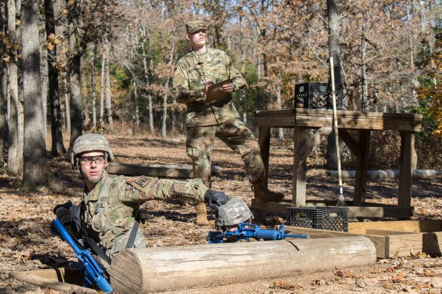 Cadet Sam Rothlisberger, left, of Marquette University, Wisconsin, throws a practice grenade toward a target while his teammate, Cadet Lindsay Walter, provides cover fire at the Hand Grenade Assault Course Nov. 1. Marquette University's nine-person team placed second overall in the competition and will go on to represent the 3rd Brigade at Sandhurst.