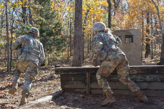 Cadets Dallas Volentine, left, and Anna Robben of Iowa State University storm a bunker to toss a practice grenade in the window at the Hand Grenade Assault Course Nov. 1. The practice grenades used by the cadets had almost no explosive power, using only a blasting cap for audible effect.