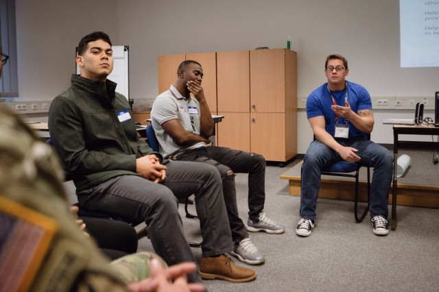 U.S. Air Force Staff Sgt. Adam Spittle (right), assistant instructor, 7th Weather Squadron, leads a group discussion during an Applied Suicide Intervention Skills Training workshop where participants share experiences and draw understanding from each other's cultural backgrounds in Vilseck, Germany, Nov. 6, 2019. ASIST is a workshop that trains leaders in life-saving suicide intervention skills. (U.S. Army Photo by Sgt. Timothy Hamlin, 2d Cavalry Regiment.)