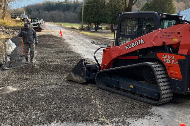 New York Air National Guard Master Sgt. Roger Yurko, the 109th Airlift Wing Emergency Management directs Staff Sgt Kaitlyn Keefe as she operates a Kabota Skid Steer to rebuild a shoulder on White Creek Road in the town of Newport, Herkimer County, N.Y, on Nov. 3, 2019. The 109th Airlift Wing dispatched its debris clearance team and general-purpose forces in support of the New York National Guard effort to assist the county after a major storm on Halloween night, 2019.